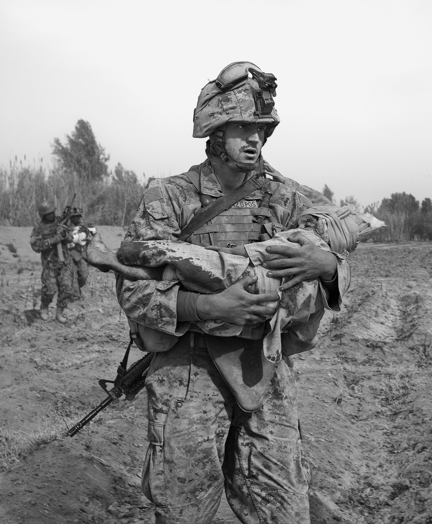 A Marine carries an Afghan child, one of two wounded by coalition aircraft during an air support mission.