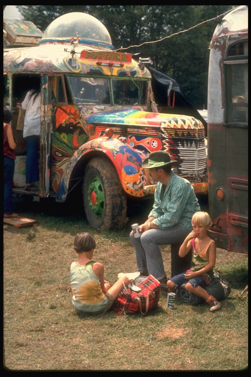 A man sits with two young boys in front of Ken Kesey's legendary Merry Prankster bus, Further. (See the sign above the windshield.)  I got a nice picture of that painted hippie bus, with a couple of kids and what I think might be their father. Whoever painted that thing really did a beautiful job!