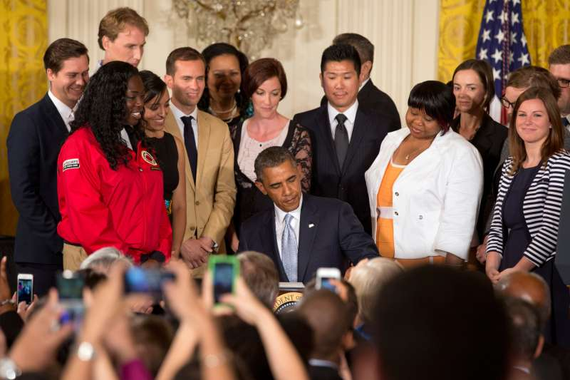 Surrounded by college students, President Barack Obama signs a presidential memorandum on reducing the burden of student loan debt, Monday, June 9, 2014, in the White House East Room.