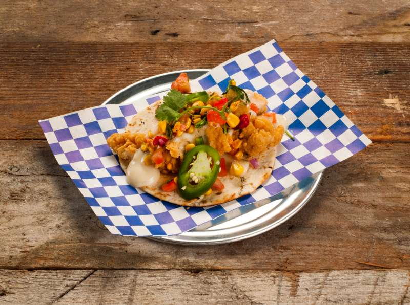 U.S. Taco Co. features china plates and a menu that includes lobster, fried chicken, and pulled pork tacos. What you won't find is any branding that connects it to parent Taco Bell.