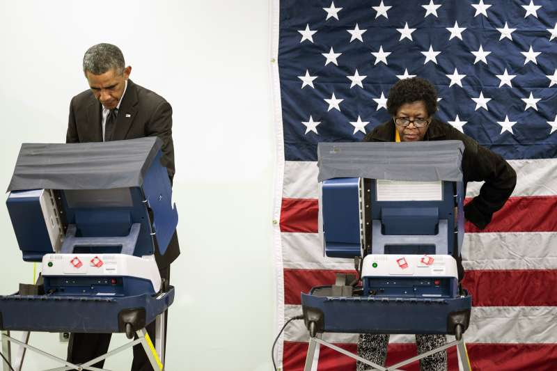 President Barack Obama(L) casts a ballot in early voting for the 2014 midterm elections at the Dr. Martin Luther King Community Service Center October 20, 2014 in Chicago, Illinois.  The President took a break from campaigning for Democratic Governor Pat Quinn to cast his vote.