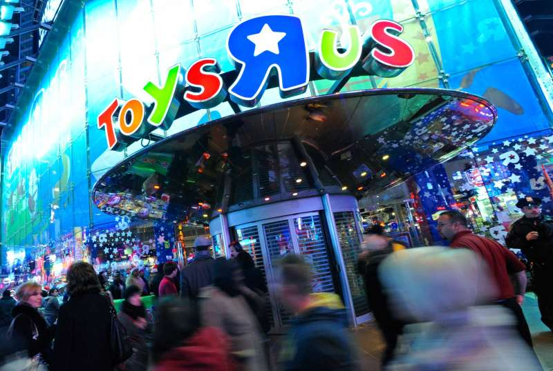Pedestrians walk by a Toy  R  Us Inc. store during a Black Friday sale in New York, in 2011.