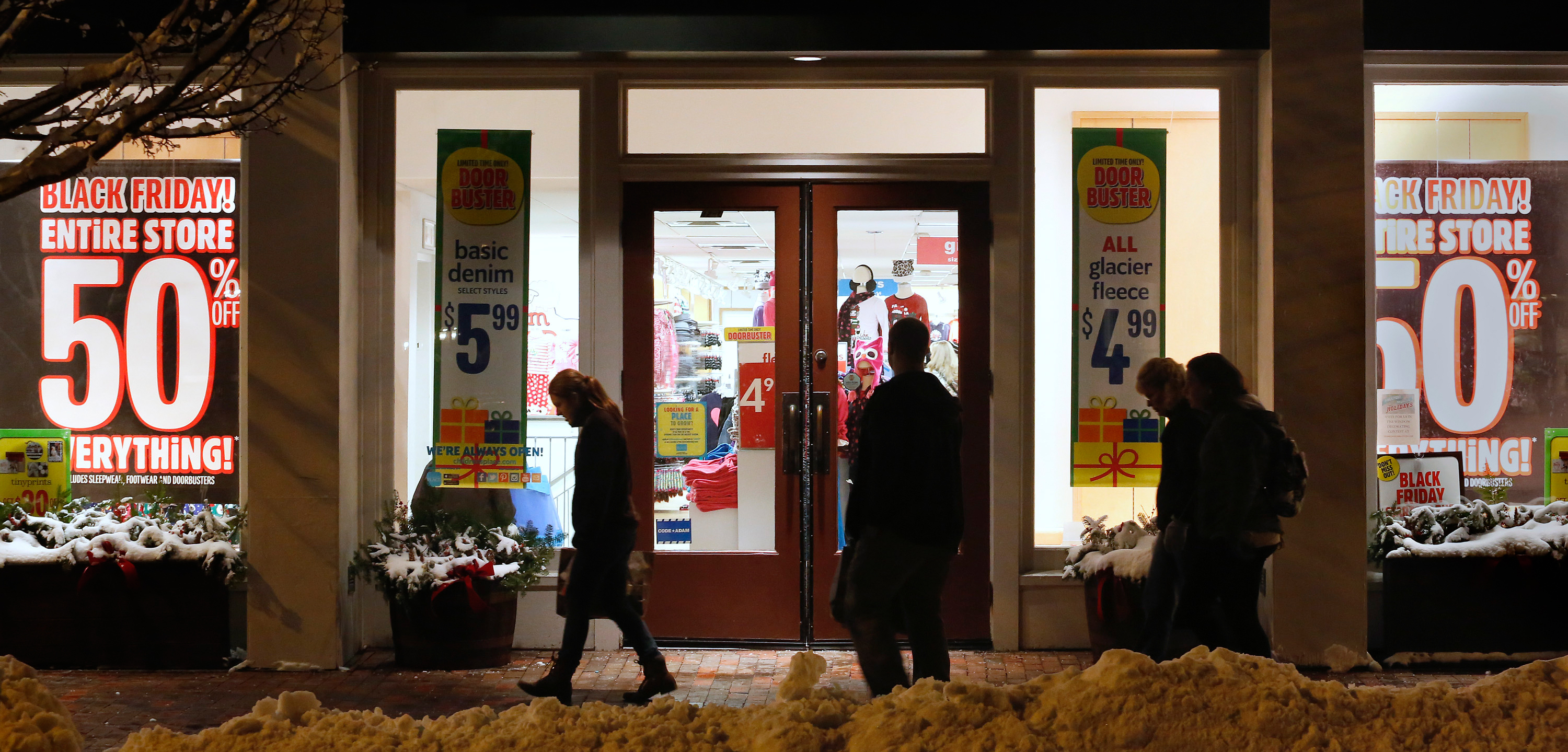 Shoppers pass by stores windows advertising Black Friday deals after the stores opened their doors at midnight.