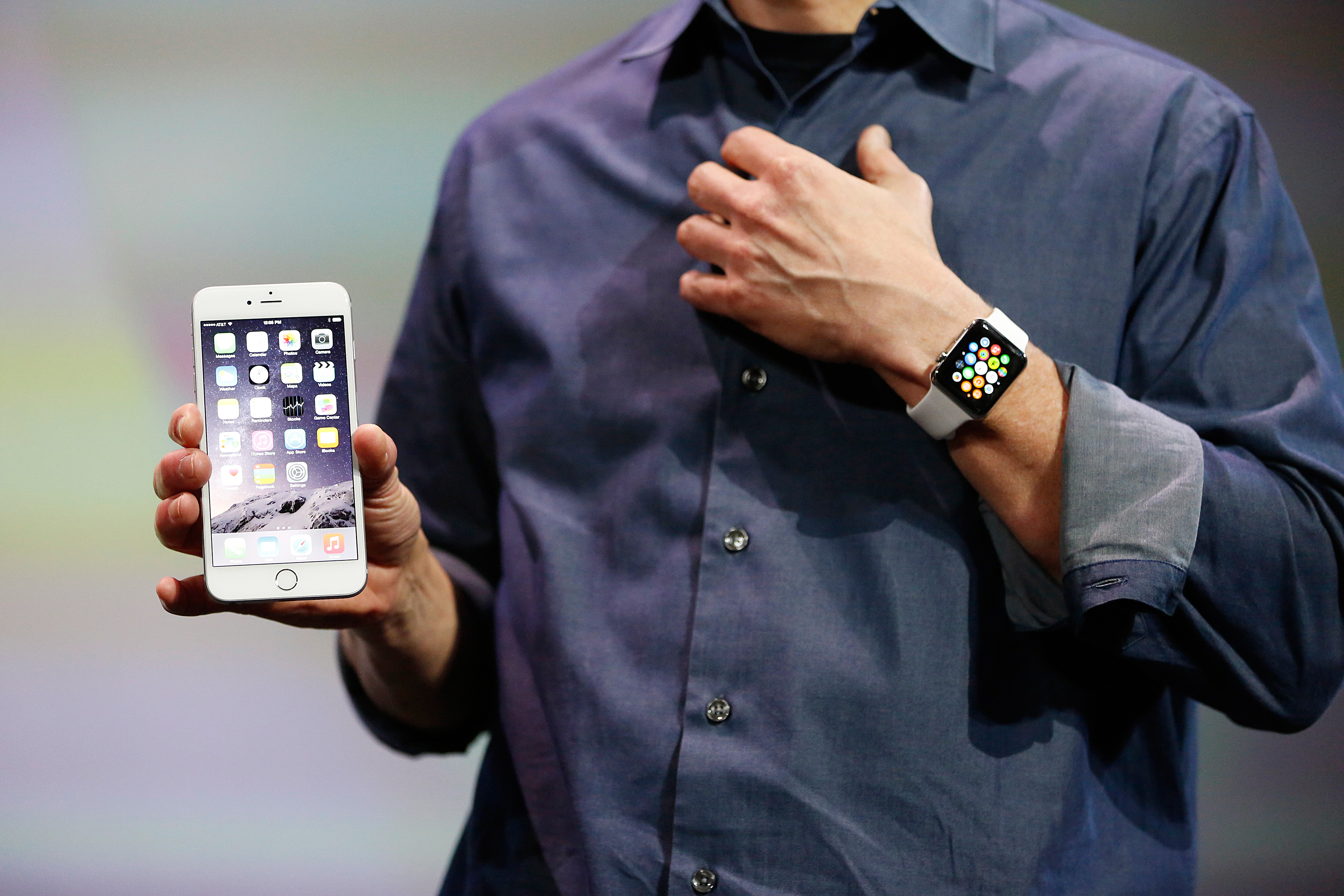 Apple CEO Tim Cook wears the Apple Watch and shows the iPhone 6 Plus during an Apple event at the Flint Center in Cupertino, California, September 9, 2014.
