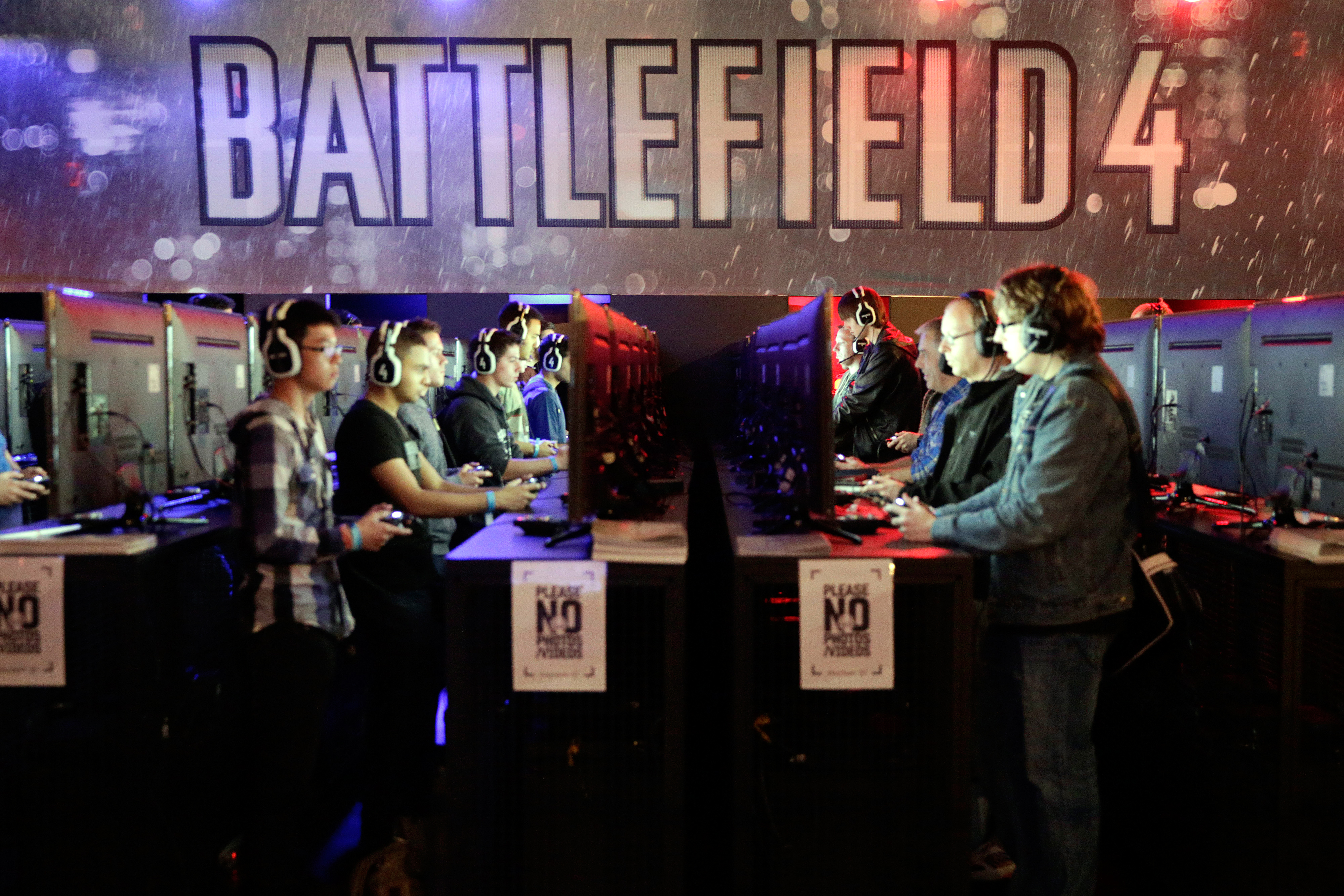 Gamers wear headsets as they play Electronic Arts Inc.'s  Battlefield 4  video game on Microsoft Corp. Xbox One games consoles.