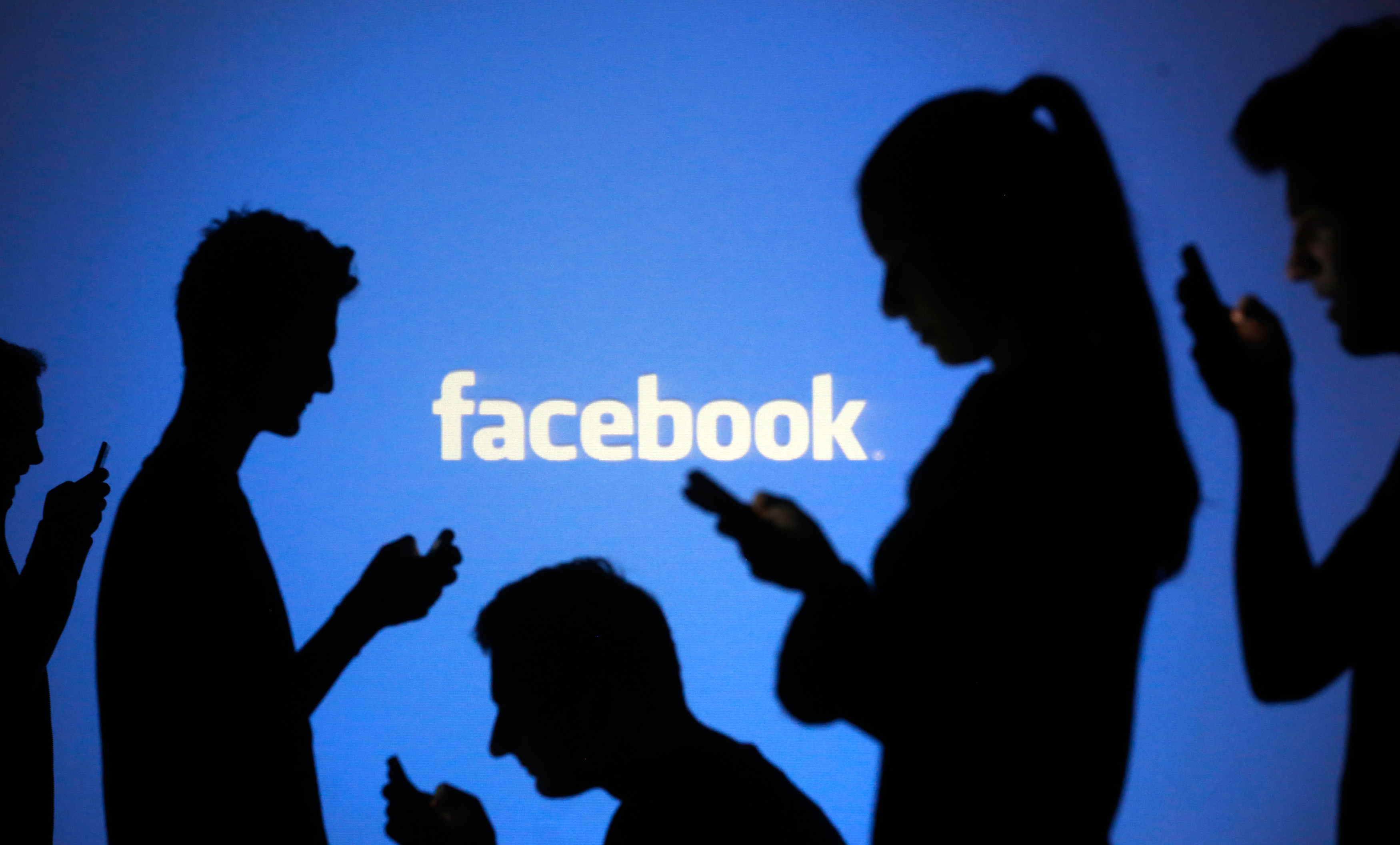 silhouettes of people using mobiles in front of FAcebook logo