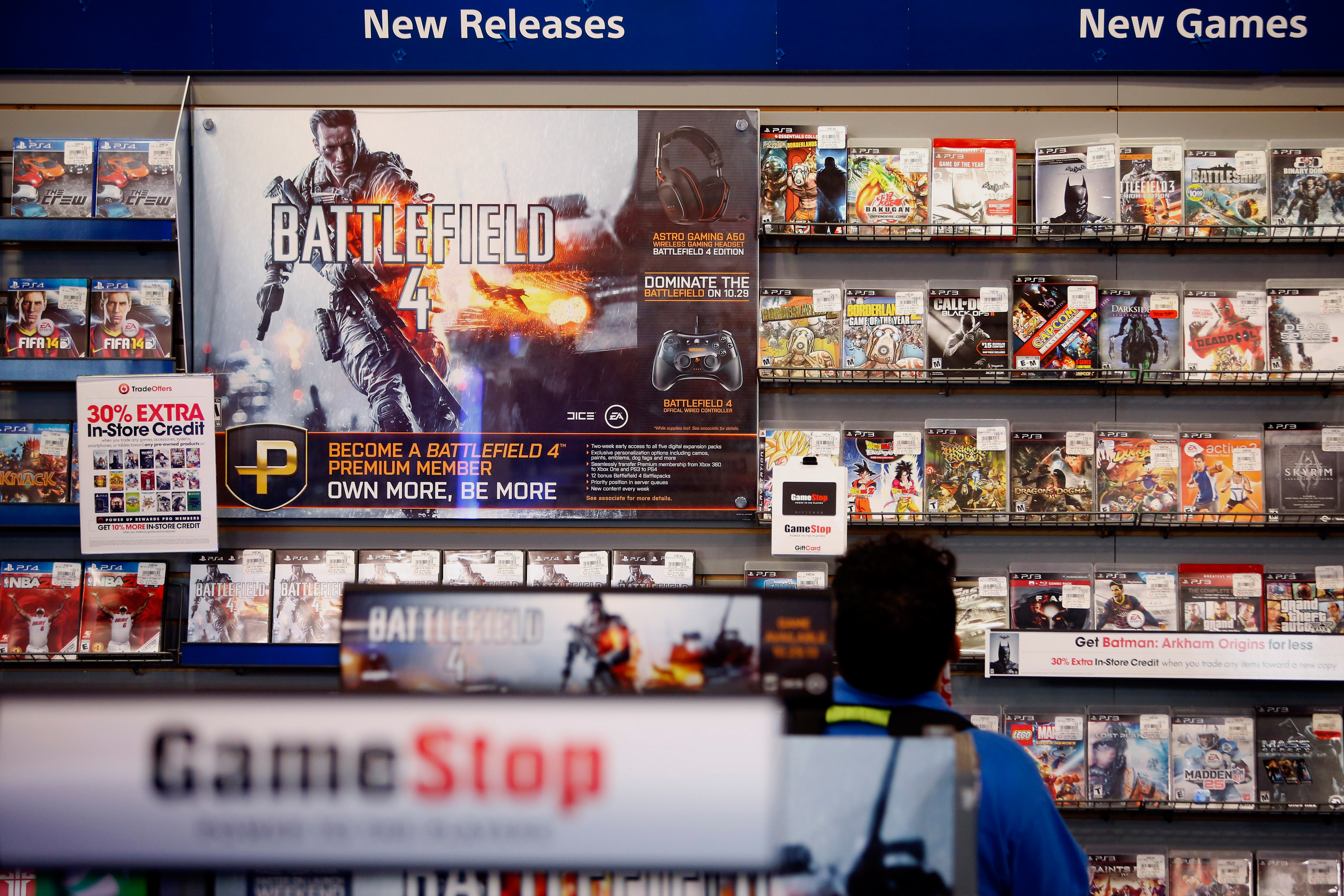 An Electronic Arts Inc. Battlefield 4 video game advertisement is displayed as a customer browses at a GameStop Corp. store in West Hollywood, California, U.S.