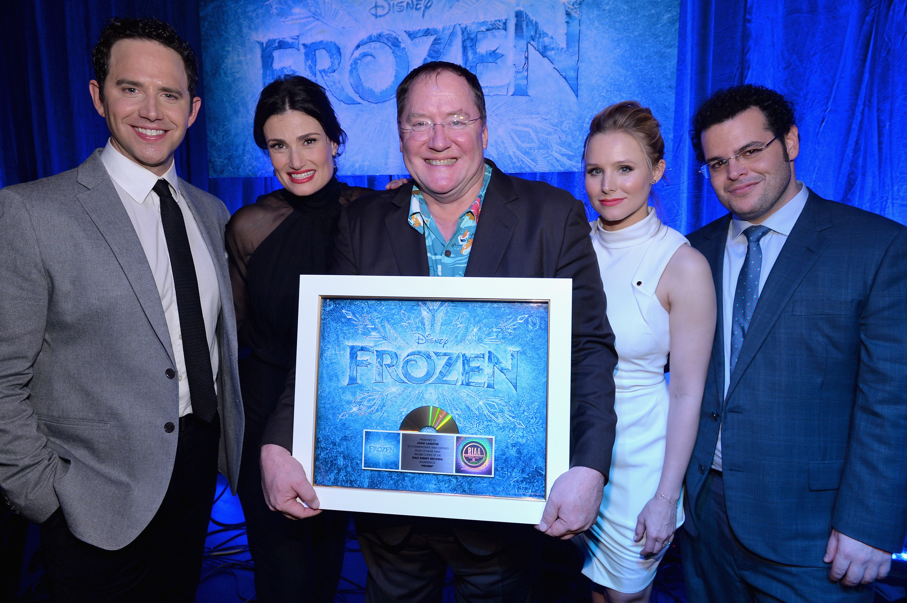 Executive producer John Lasseter (C) and the cast of Disney's  Frozen  were presented with gold records commemorating the success of the  Frozen  soundtrack.