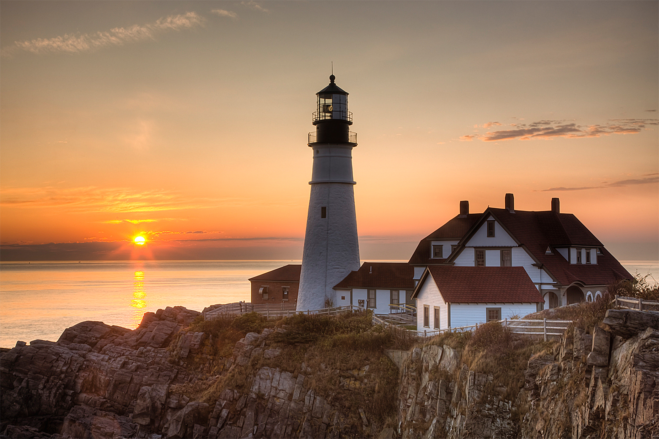 The first rays of sun after sunrise reach the Portland Head Light, built in 1791, which protects mariners entering Casco Bay. The lighthouse is located in Fort Williams Park, Cape Elizabeth, Maine, USA.