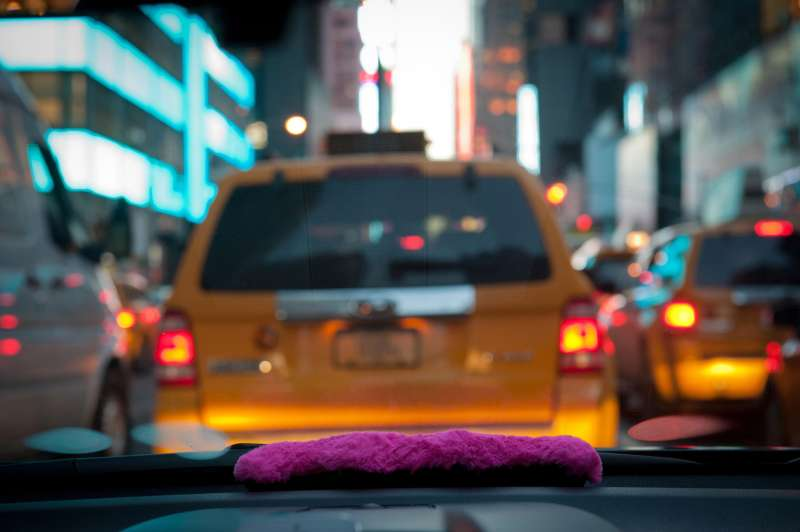 A pink mustache on the dashboard as Bouchaib El Hassani, 31, a Lyft driver, makes his way through midtown.