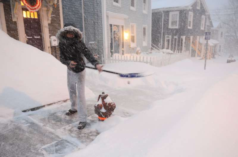 Shalonda Earvin clears the sidewalk in front of her Union St. home in Norwich, Conn., Tuesday, Jan.  27, 2015. Earvin said this was her fourth time out shoveling since it started snowing.