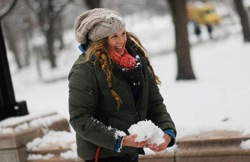 A woman gathers snow for a friendly snowball fight in Central Park.