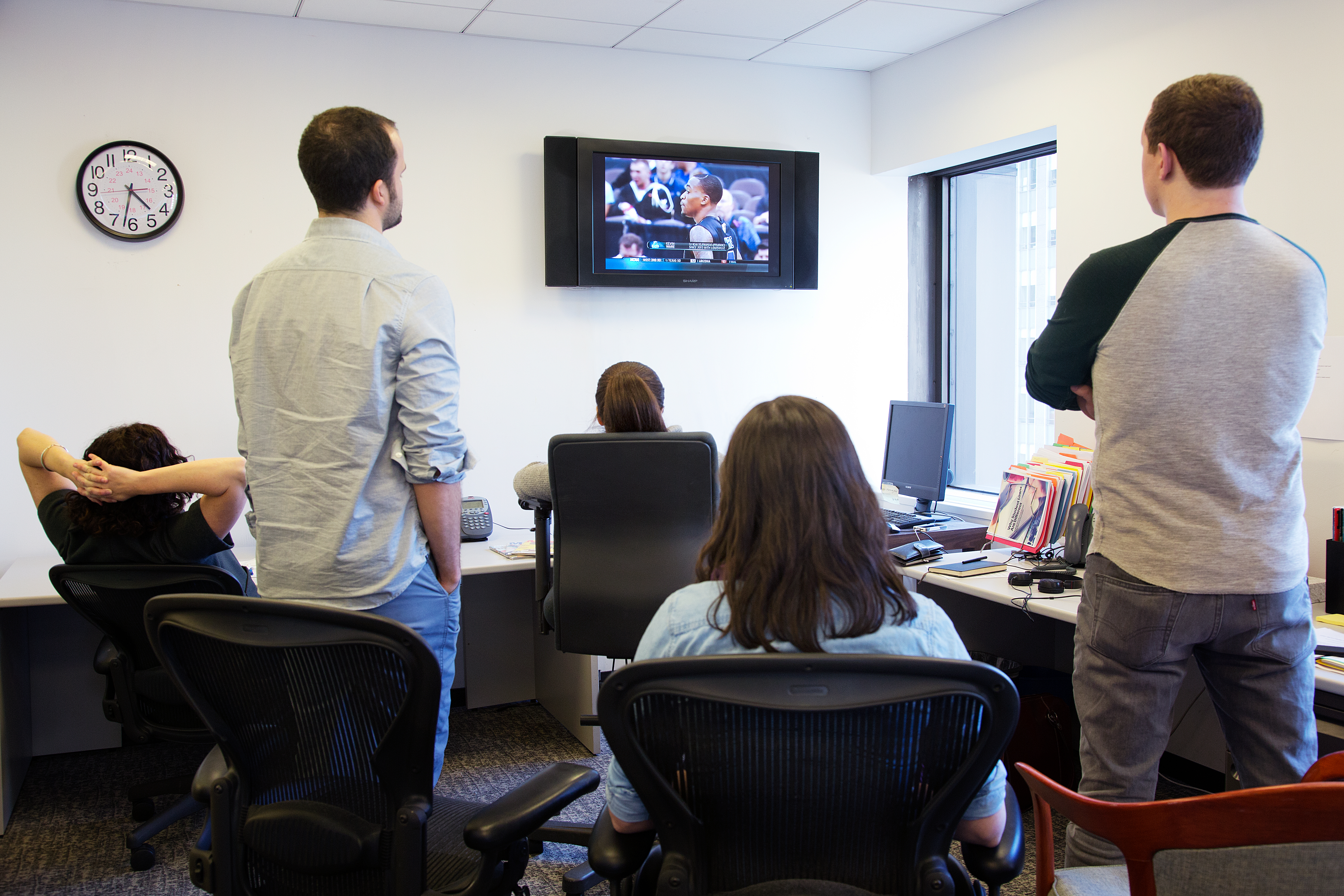 Office workers watching March Madness on television