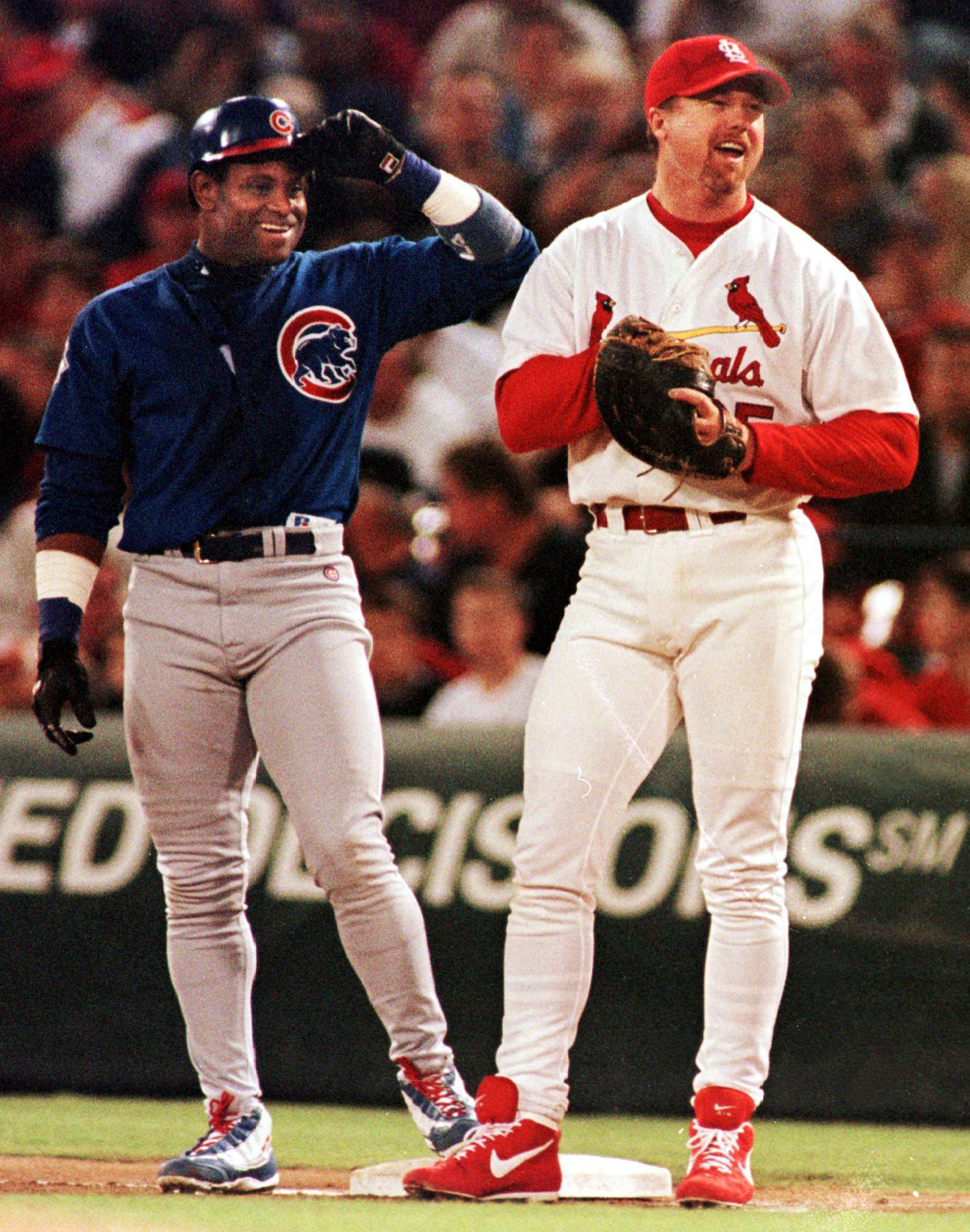 Chicago Cubs' Sammy Sosa (L), shares a laugh with St. Louis Cardinals' first baseman Mark McGwire (R), after receiving a walk in the third inning. McGwire stayed at 63 home runs and Sosa stayed at 62 as neither had a home run in the 3-2 Chicago victory.