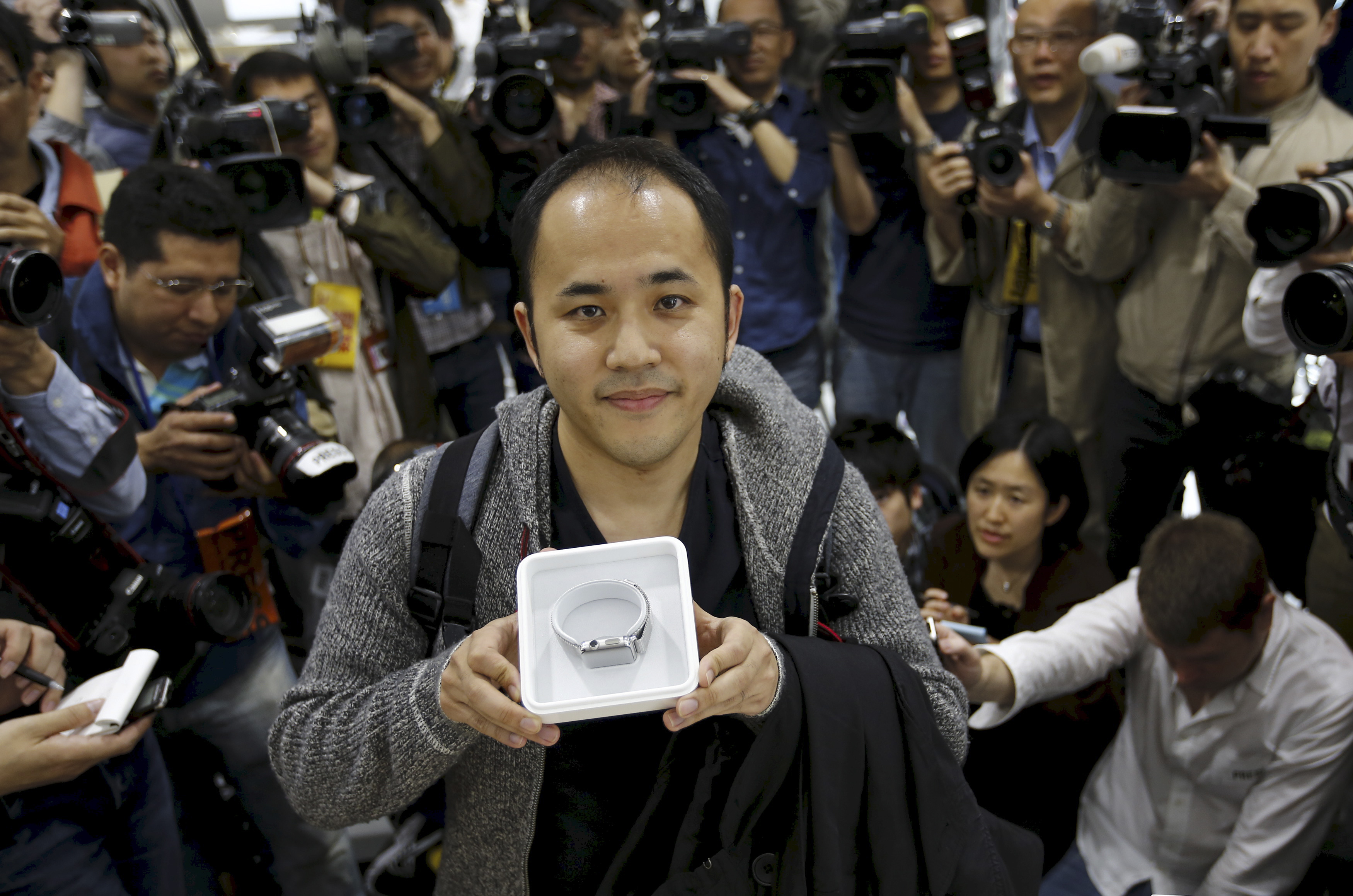 Yuichiro Masui, the first customer to purchase an Apple Watch at an electronics store in Omotasando, poses with his watch in Tokyo April 24, 2015.