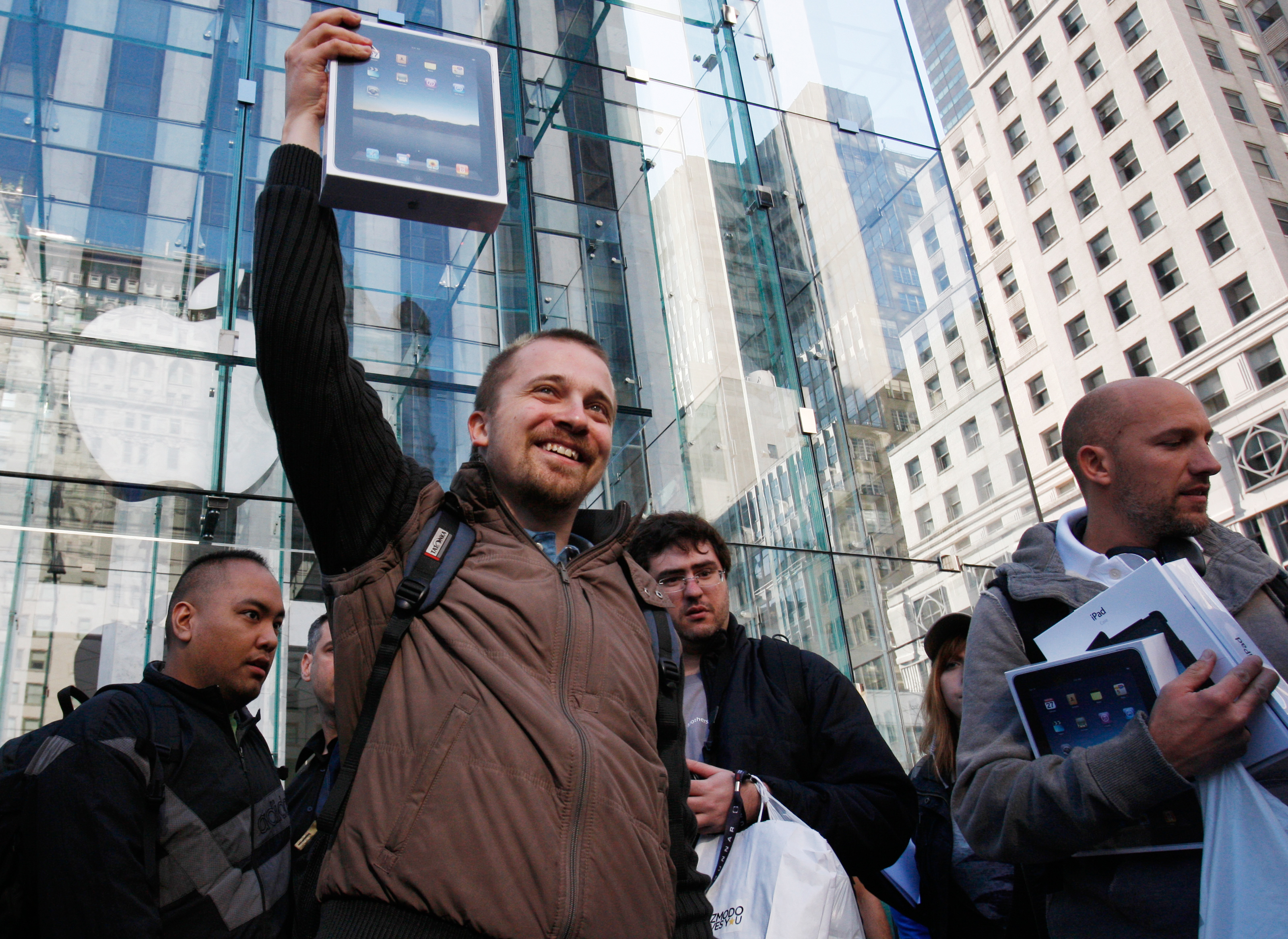A customer lifts his iPad over his head after leaving the iPad launch at the Apple Store in New York.