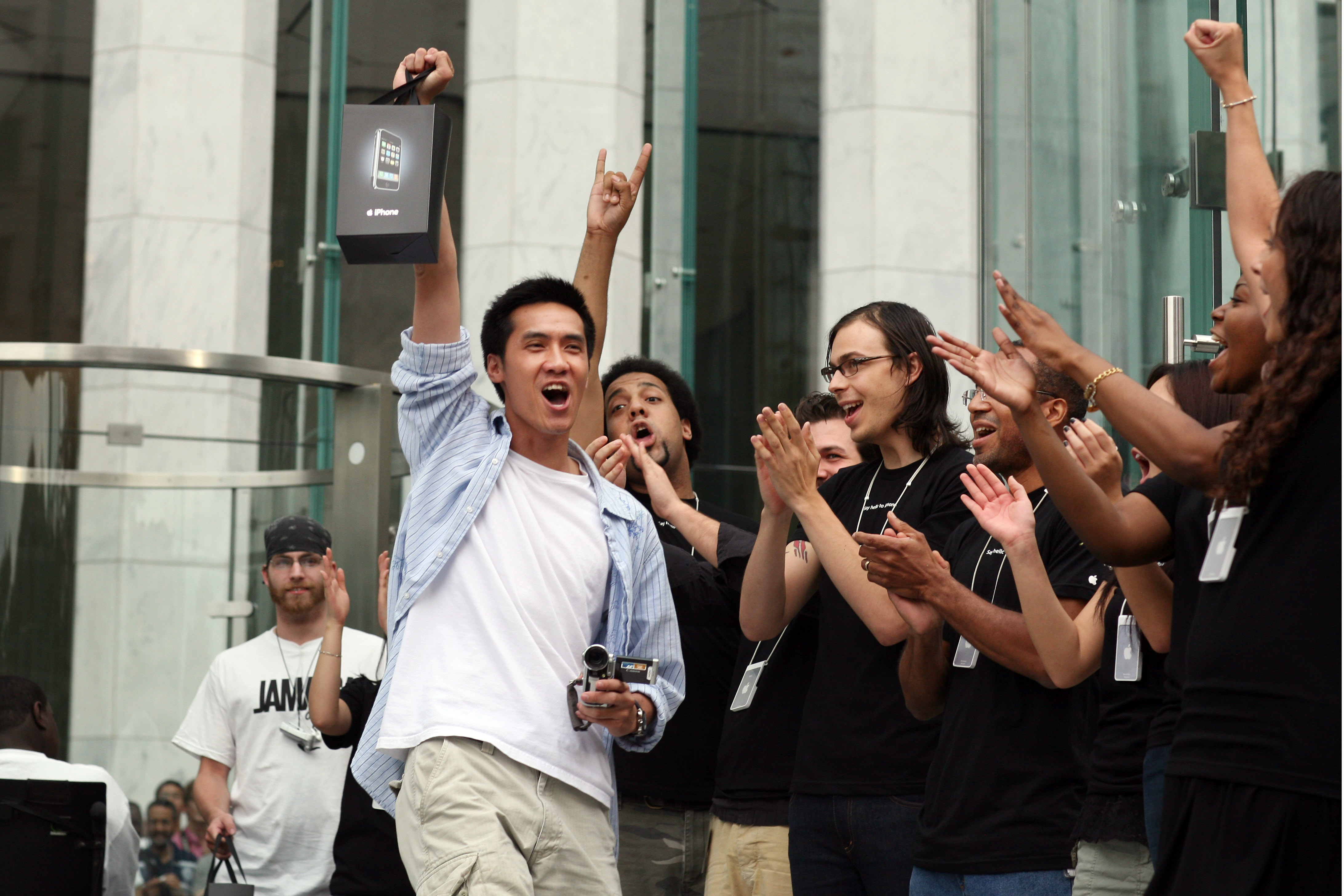 New iPhone owners exit Apple's flagship store, showing off their purchases to the media.