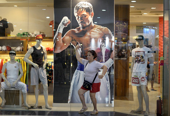 A woman poses in front of a poster of Philippine boxing icon Manny Pacquiao at a store in Manila. Manny Pacquiao's face is on shirts, dolls and postage stamps, his life story is playing in movie houses and millions are getting ready to party as the Philippine boxing hero's  fight of the century  nears.