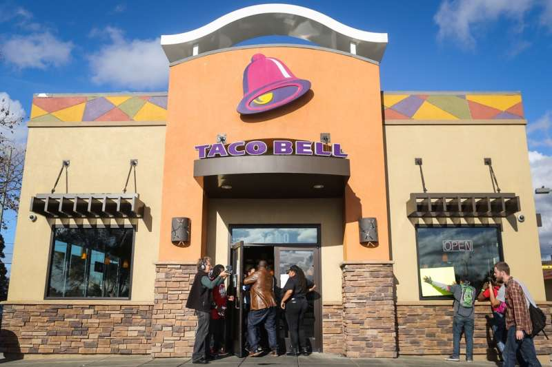 OAKLAND, CA - DECEMBER 4: Protesters enter a Taco Bell as part of a demonstration for higher wages and better security for fast food workers on December 4, 2014 in Oakland, California. The Taco Bell has been the victim of numerous violent robberies but has no security guard. The protest was part of a nationwide day of demonstrations. (Photo by Elijah Nouvelage/Getty Images)