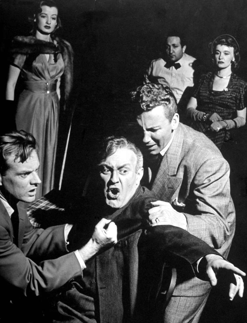 Caption from LIFE. Losing his mind as result of worry, the salesman, Willy Loman (Lee J. Cobb), babbles at imaginary characters in a restaurant. This two sons attempt to restrain him while a couple of floozies the boys have picked up look on in cold puzzlement.