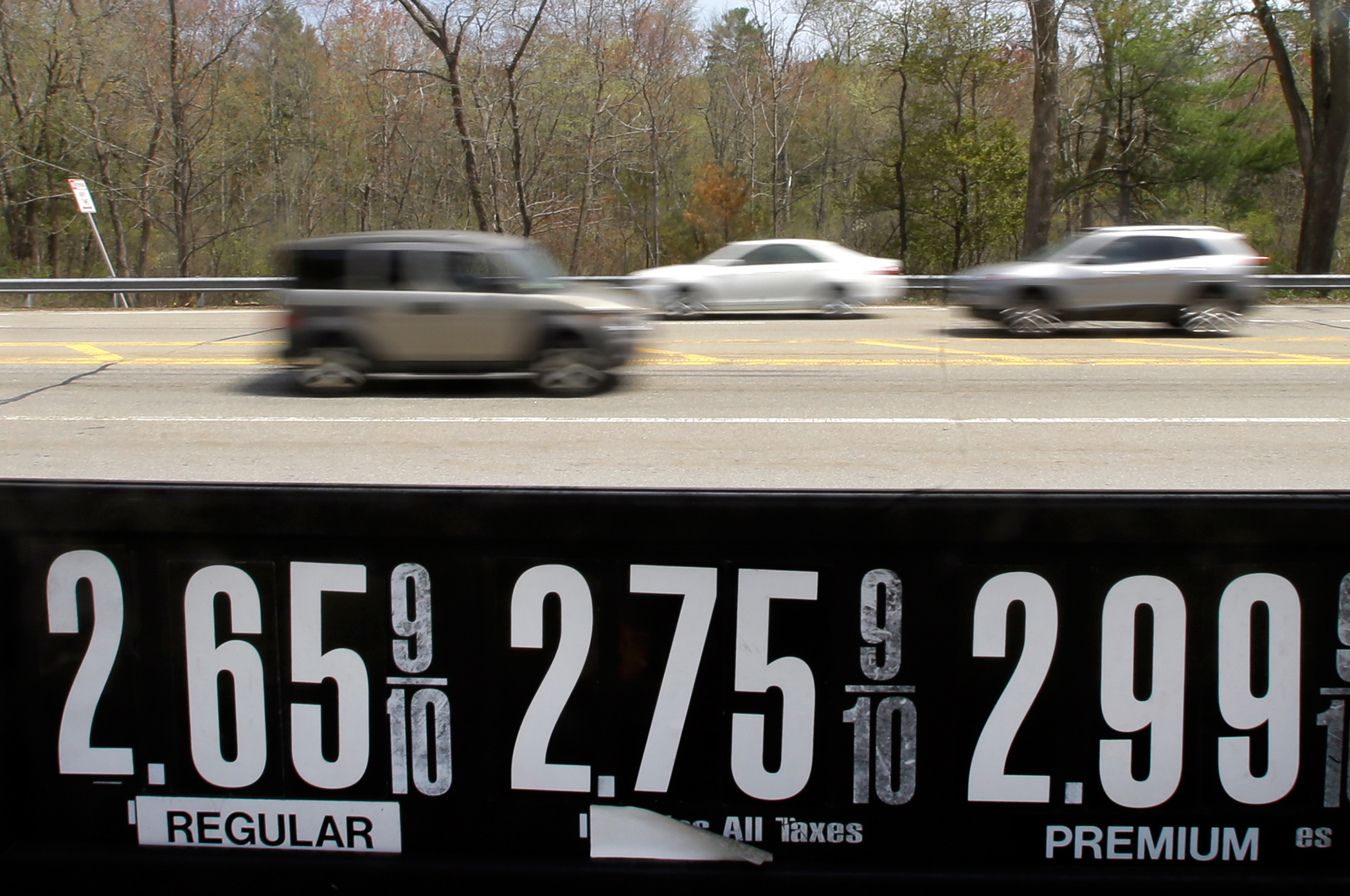 In this May 8, 2015 photo, vehicles drive past a gas station in Andover, Mass. Even after the typical springtime run-up, the average price for gallon of regular gasoline should top out around $2.60.