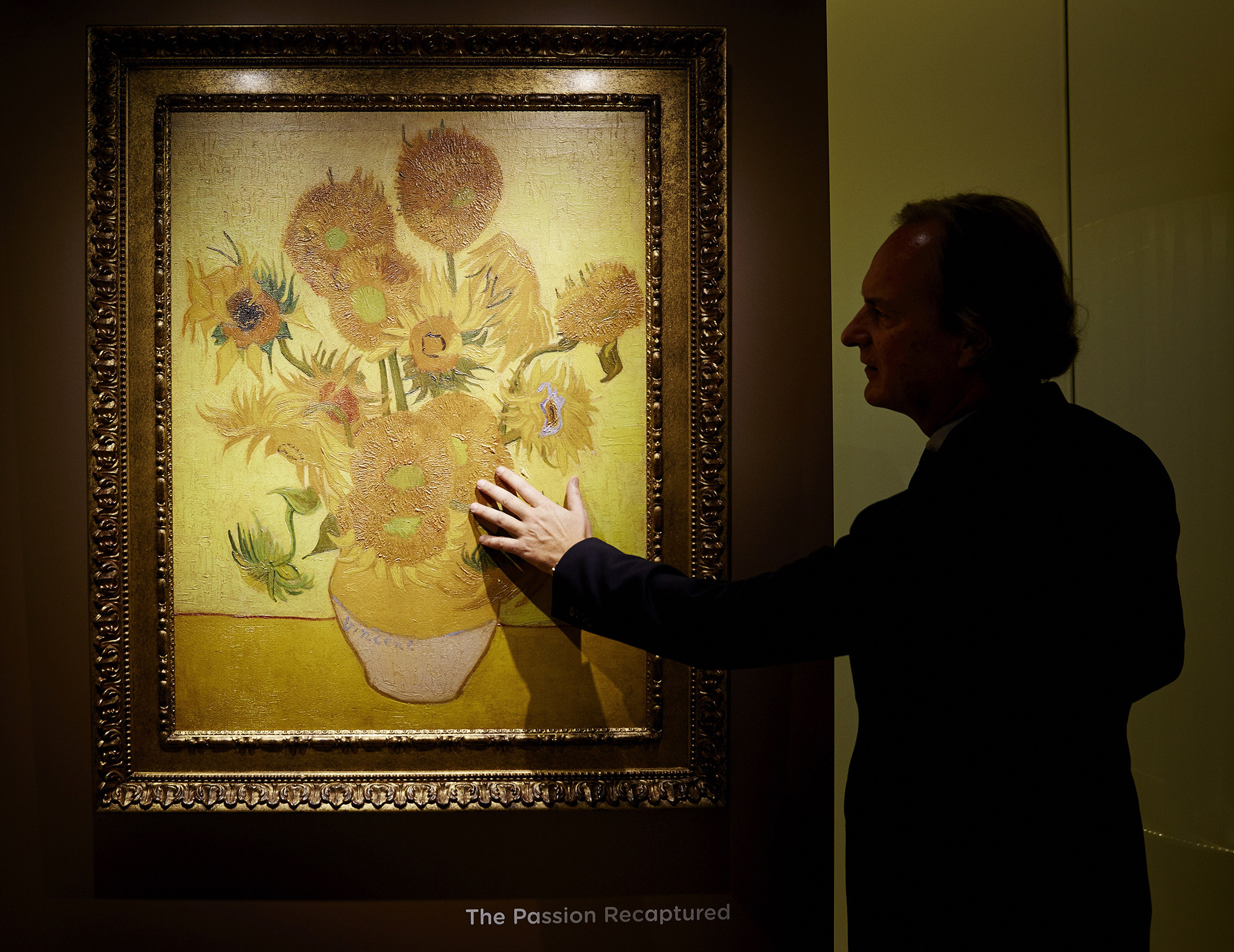 A man looks at a 'relievo', a three-dimensional reproduction of the of Vincent van Gogh's The Sunflowers on December 12, 2013 in Schiphol Amsterdam Airport.
