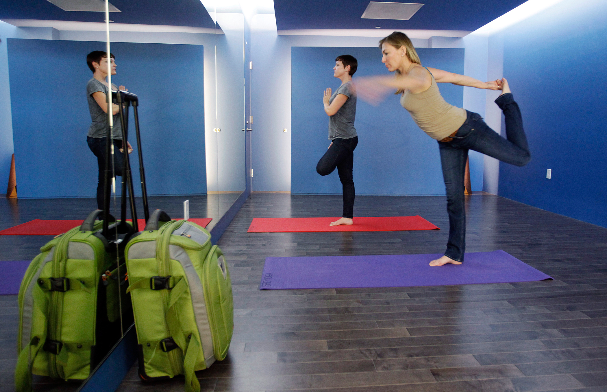 In this Friday, Jan. 27, 2012 photo, travelers Maria Poole, right, and Lindsey Shepard, practice yoga at San Francisco International Airport's new Yoga Room, in San Francisco. The quiet, dimly lit studio officially opened last week in a former storage room just past the security checkpoint at SFO's Terminal 2. Airport officials believe the 150-square-foot room with mirrored walls is the world's first airport yoga studio, said spokesman Mike McCarron.