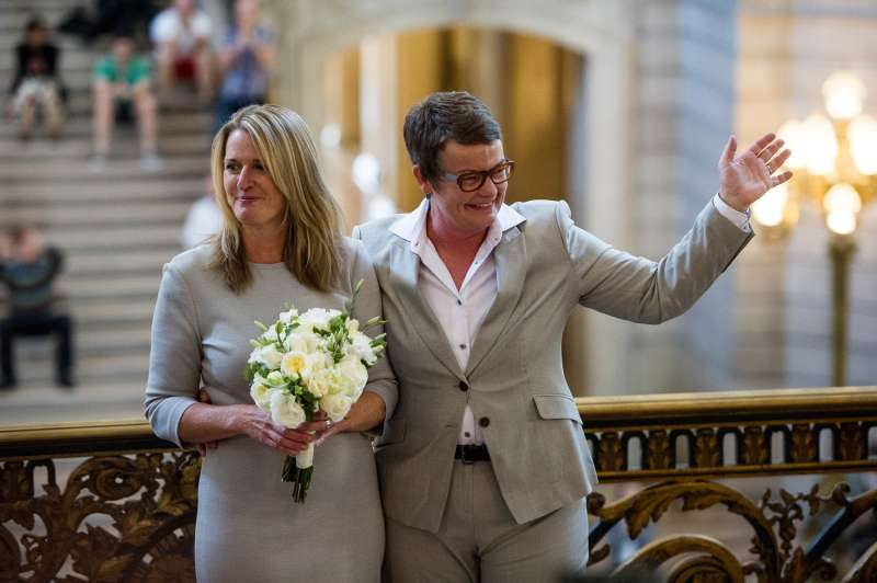 Sandy Stier, left, and Kris Perry wave to supporters after being married in City Hall in San Francisco, California, U.S., on Friday, June 28, 2013.