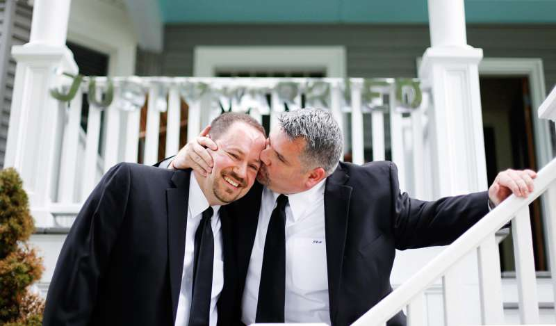 Jay Norris gives his partner, Doug Fillmore, a kiss under a Just Married sign their neighhbors put up for them at their home on the Eastern Promenade in Portland, Maine.