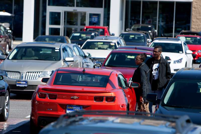 Customers check out a vehicle on the sales lot at a CarMax Inc. dealership in Brandywine, Md., on March. 29, 2015.