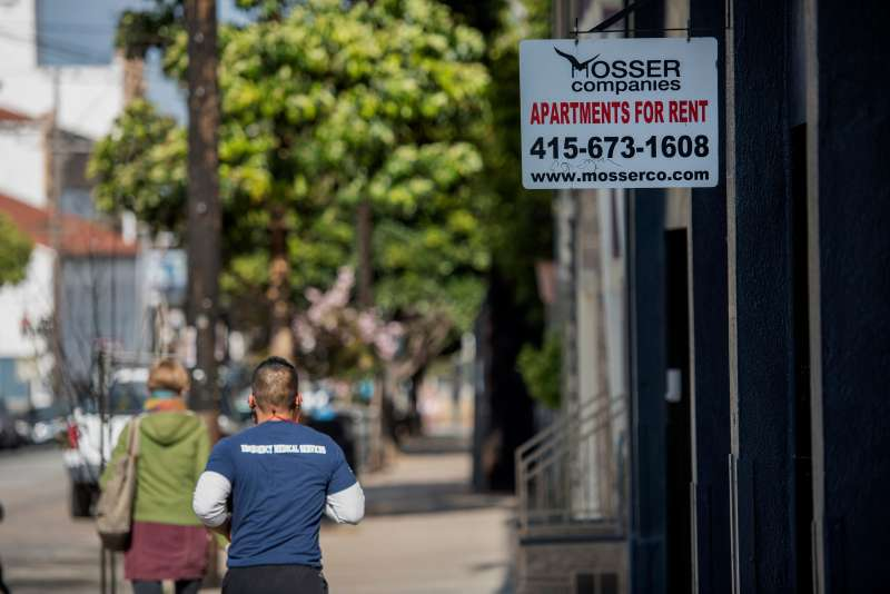 Pedestrians walk past a  For Rent  sign that is displayed outside of an apartment building in the Mission district of San Francisco, California, U.S., on Thursday, May 7, 2015.