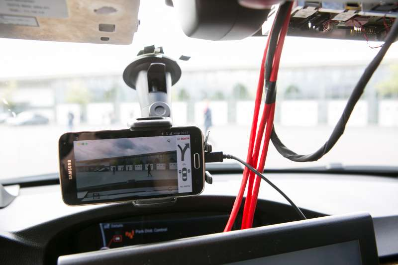 A Samsung Electronics Co. smartphone camera displays a wrong-way driver warning app as it sits on the windshield of a Bayerische Motoren Werke AG (BMW) 3 Series automobile at the Robert Bosch GmbH driverless technology press event in Boxberg, Germany, on Tuesday, May 19, 2015.