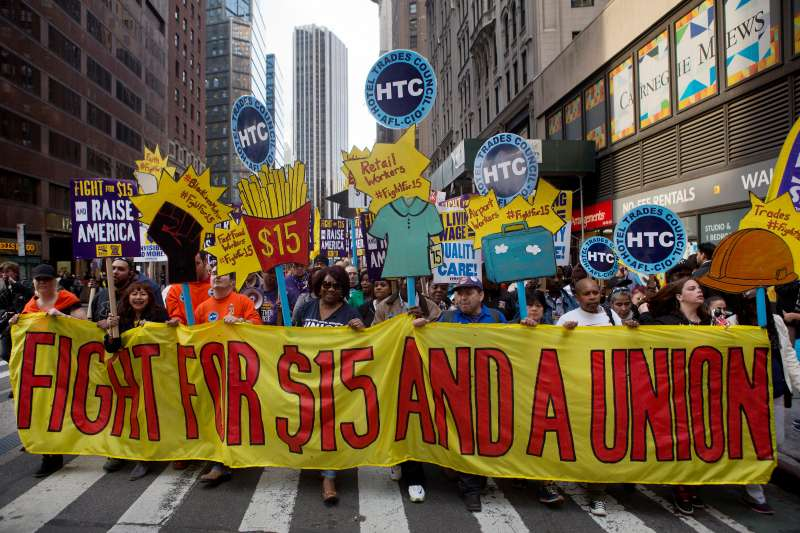 Protesters hold signs at a rally in support of minimum wage increase in New York, U.S., on Wednesday, April 15, 2015.