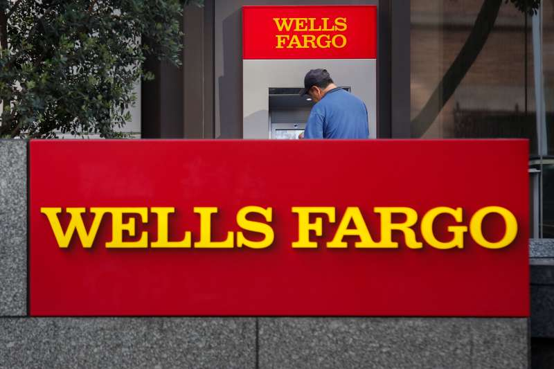 A man uses an ATM outside of a Wells Fargo & Co. bank branch in Los Angeles, California, U.S., on Tuesday, July 7, 2015.