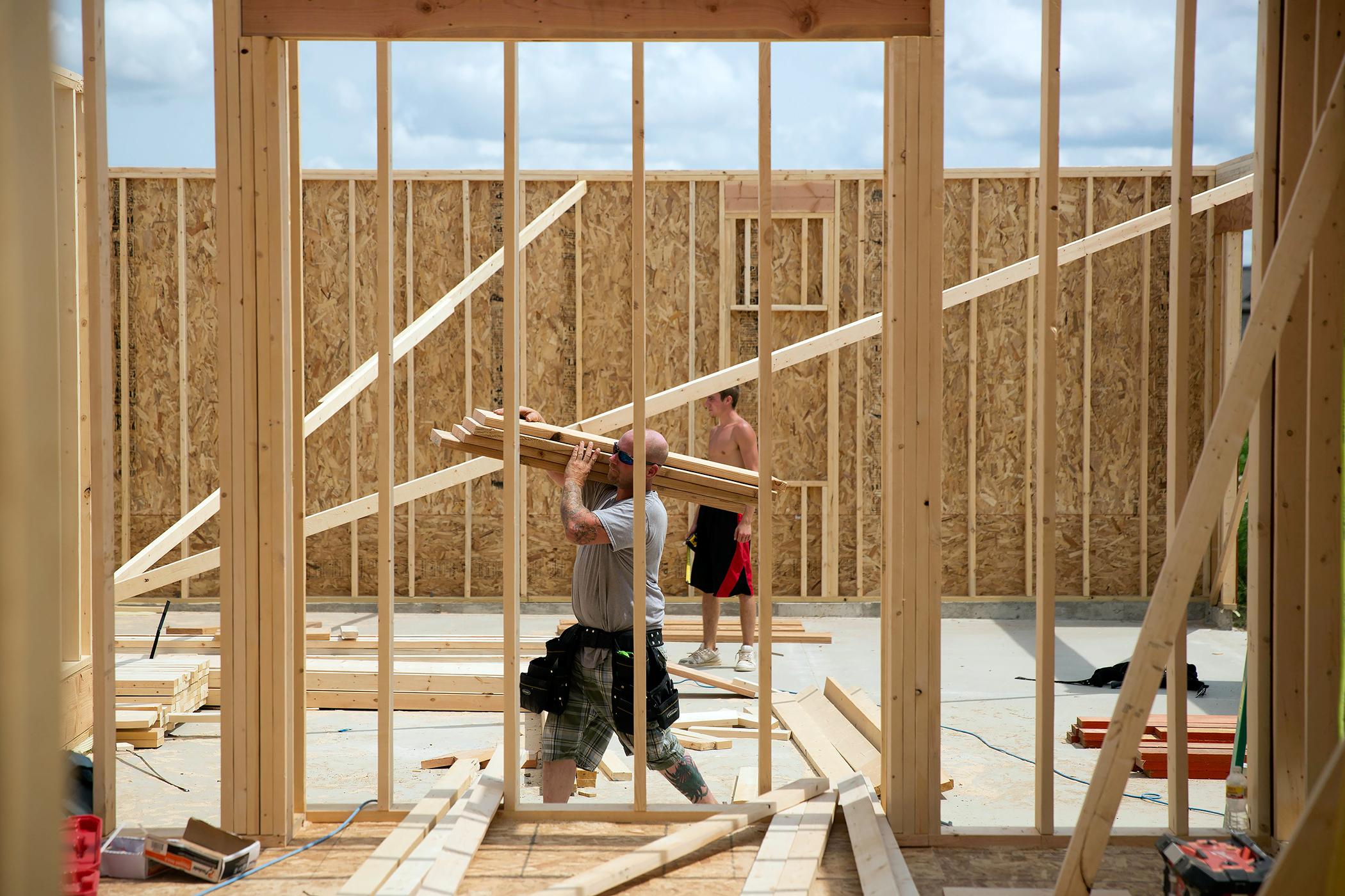 A carpenter carries lumber inside a house under construction.
