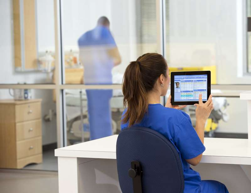 Physician Assistant using a tablet in a hospital
