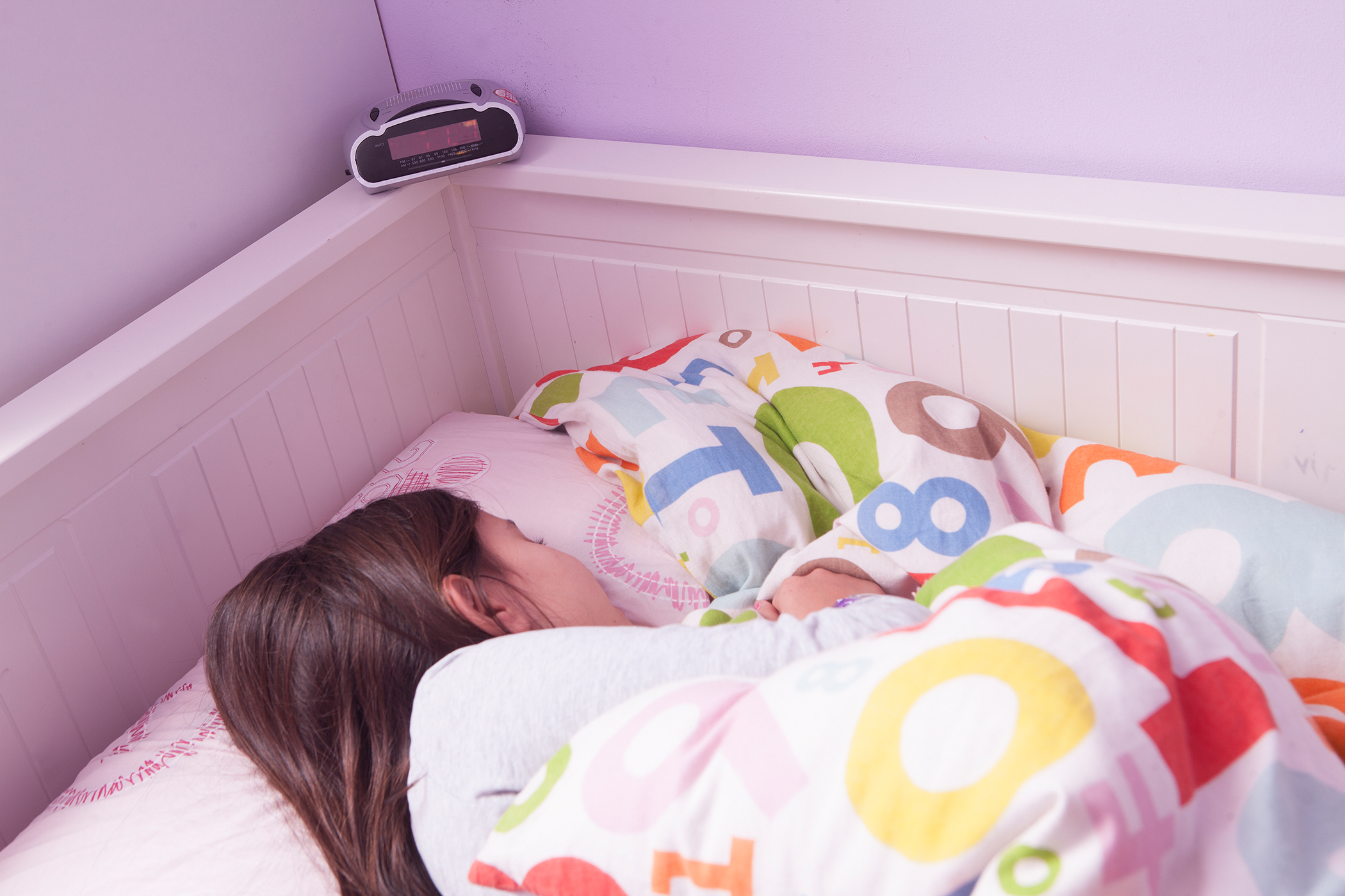 girl in bed sleeping with alarm clock