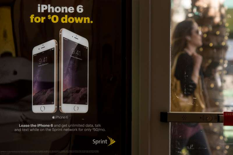 Signage advertising an Apple iPhone 6 subscription plan is displayed at a Sprint Corp. store in Palo Alto, California, U.S., on Friday, May 1, 2015.