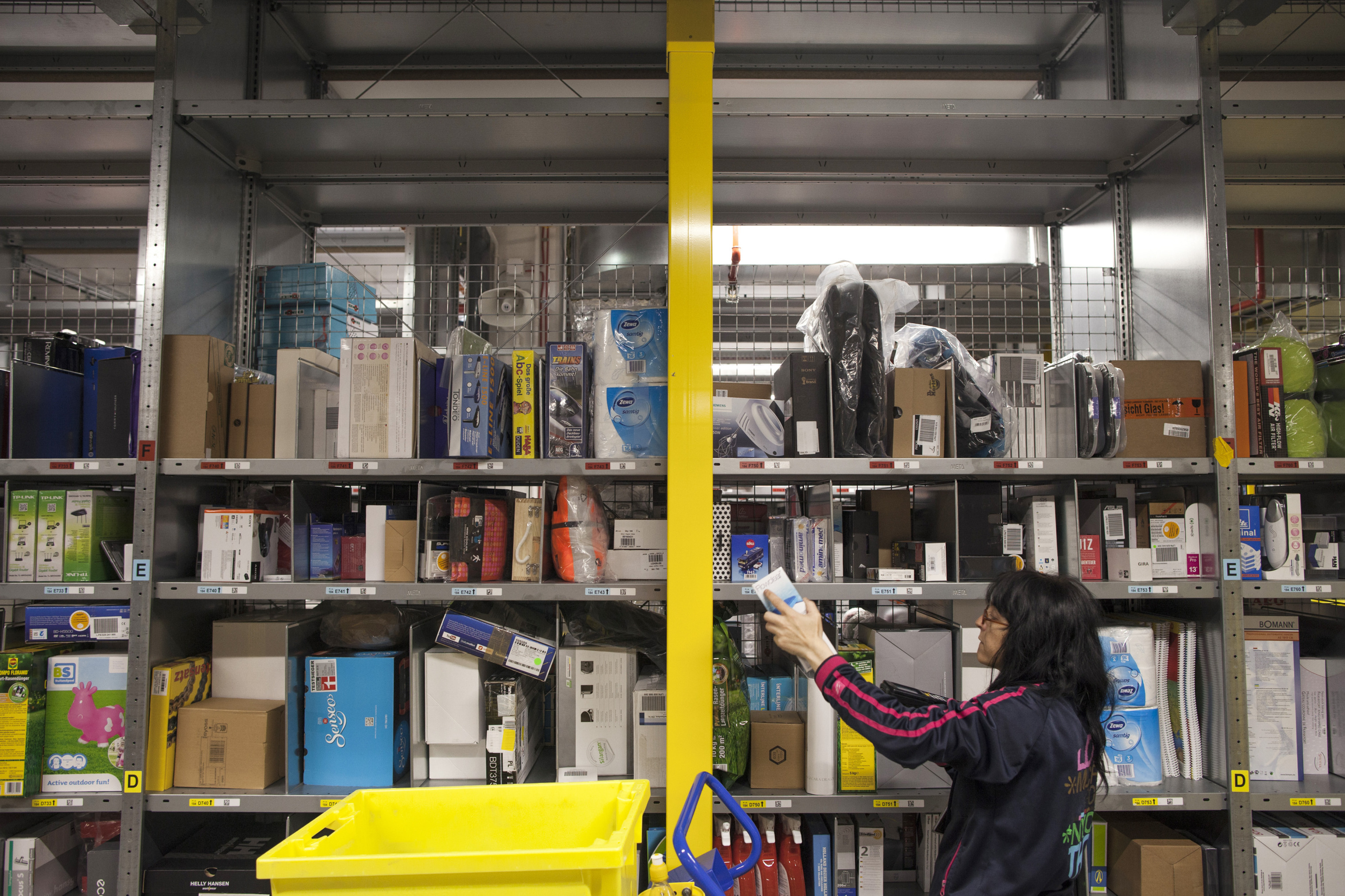 An employee selects goods from bays of merchandise as she processes customer orders at the Amazon.com Inc. fulfillment center in Poznan, Poland, on Friday, June 12, 2015.