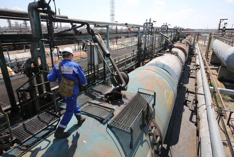 A worker walks along the top of a tank wagon as it is filled with petroleum ahead of shipping by rail at the Atyrau oil refinery, operated by KazMunaiGas National Co., in Atyrau, Kazakhstan, on Thursday, July 2, 2015. Kazakhstan is the former Soviet Union's second-largest oil producer.