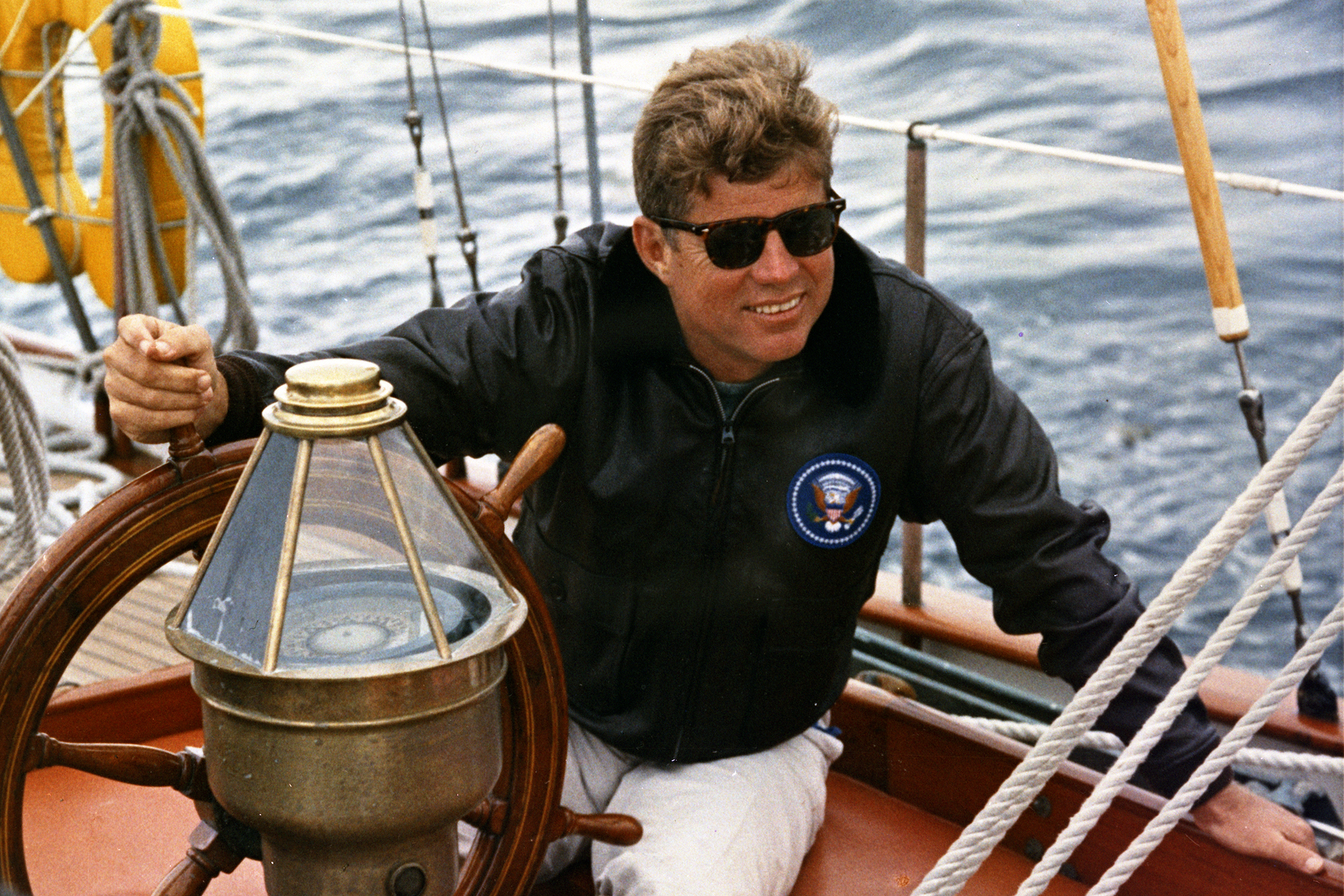 President Kennedy sails aboard the Manitou off the coast of Maine, 12 August 1962.