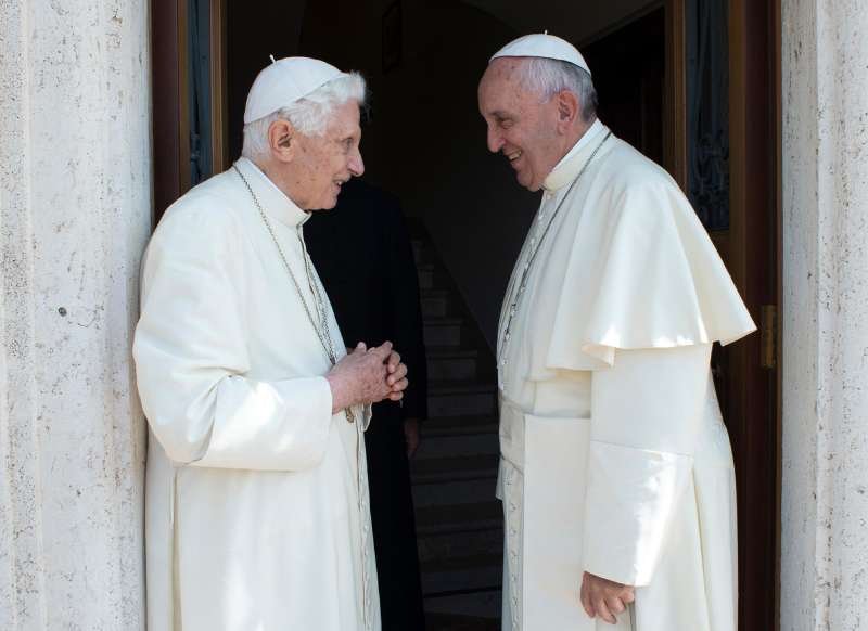 Pope Francis, right, greets Emeritus Pope Benedict XVI, at the Vatican, June 30, 2015. Emeritus Pope Benedict XVI is leaving the Vatican for his first sojourn since retiring.