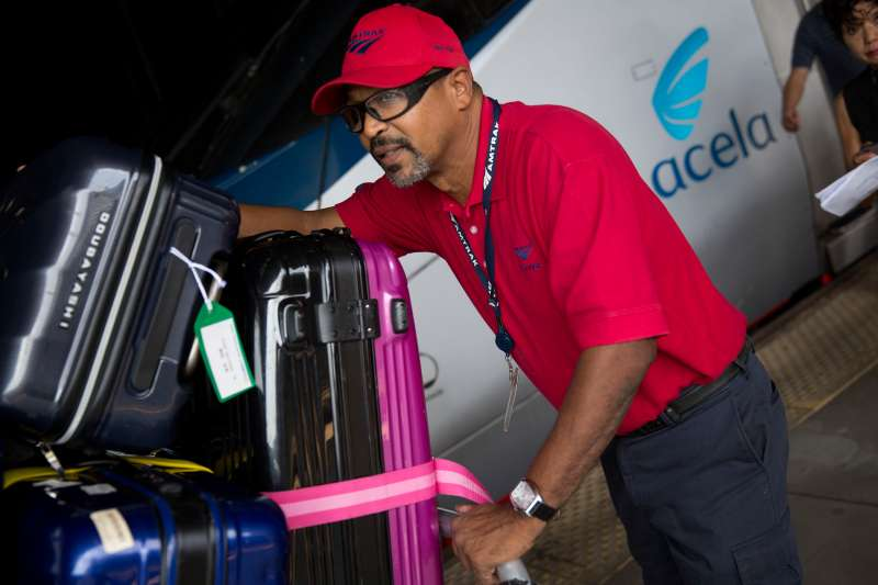 An Amtrak red cap baggage handler pushes a cart next to an Amtrak Acela passenger train at Union Station in Washington, D.C., U.S., on September 3, 2015.