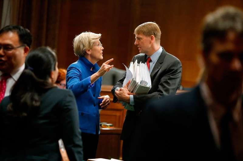 U.S. Senator Elizabeth Warren (D-MA) (L) talks with U.S. Consumer Financial Protection Bureau Director Richard Cordray (R)