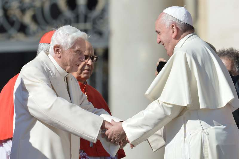 Pope emeritus Benedict XVI speaks with Pope Francis during a papal mass for elderly people at St Peter's square on September 28, 2014.