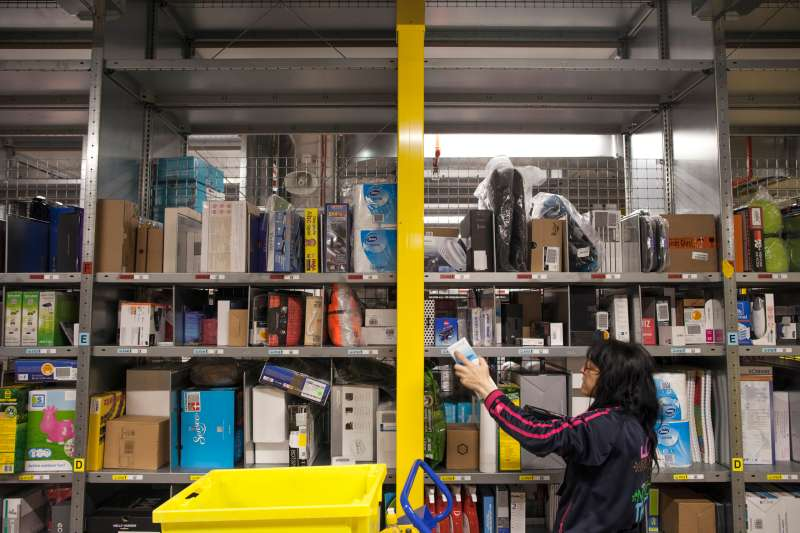 An employee selects goods from bays of merchandise as she processes customer orders at the Amazon.com Inc. fulfillment center in Poznan, Poland, on Friday, June 12, 2015. A