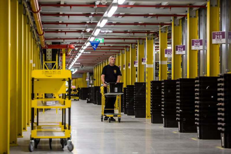 An employee wheels a cart past product storage bays on the opening day of the new Amazon.Com Inc. fulfillment center in Dobroviz, Czech Republic, on Tuesday, Sept. 8, 2015.