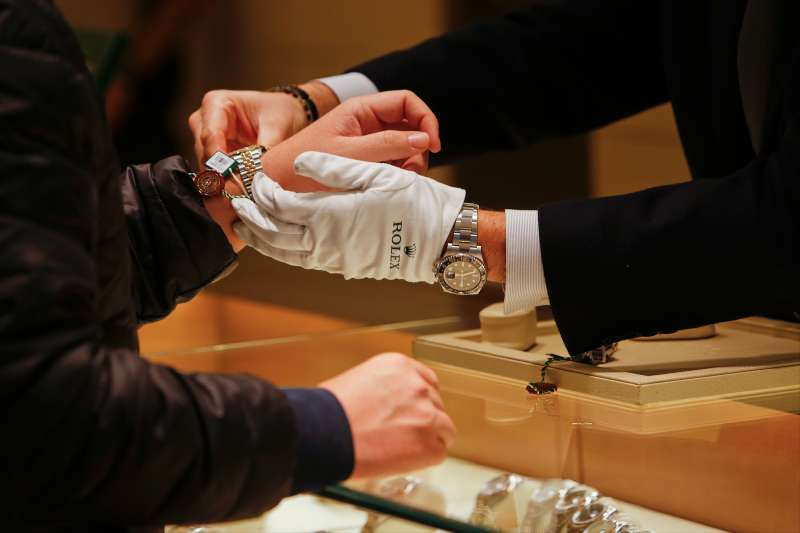 A salesman fits a Rolex Group watch onto a customer's wrist at the GEARYS Rodeo Drive Rolex store in Beverly Hills, California, on December 9, 2013.