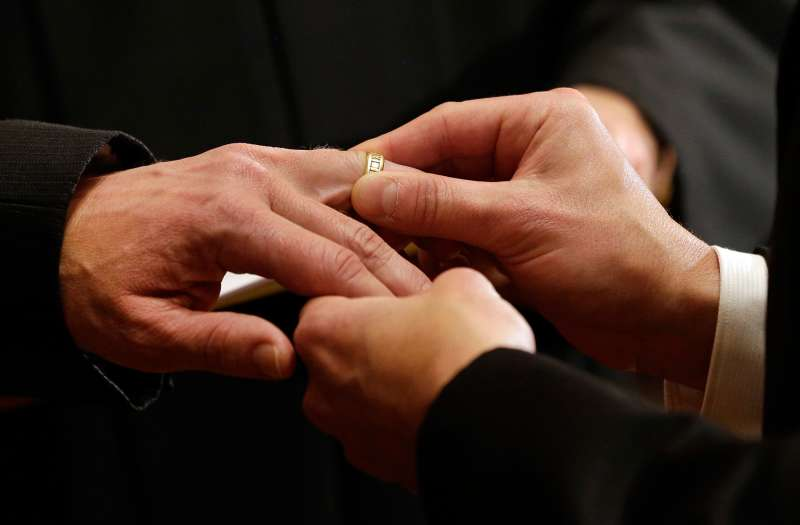Thomas Rabe, right, places a wedding ring on Robert Coffman's finger during a marriage ceremony at City Hall in Baltimore on January 1, 2013.
