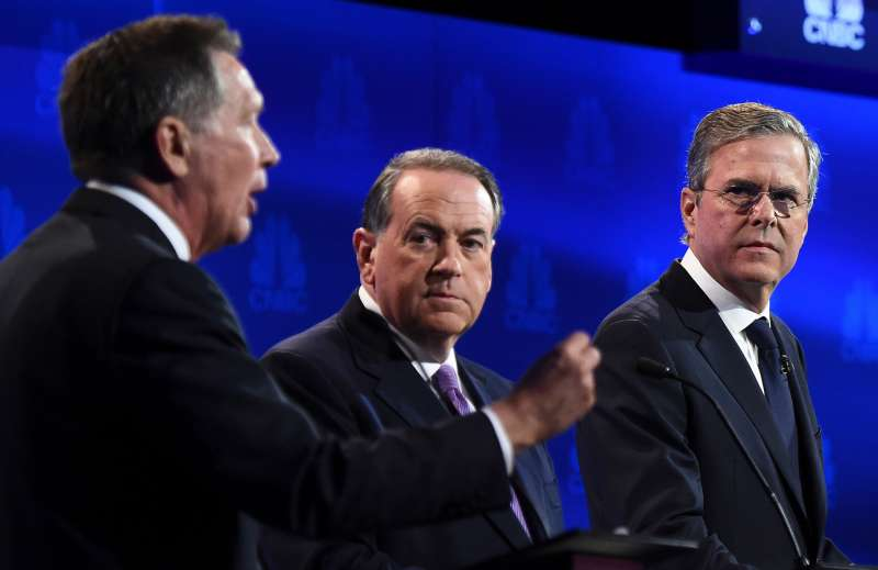 Republican Presidential hopeful John Kasich (L) speaks as Mike Huckabee (C) and Jeb Bush look on during the CNBC Republican Presidential Debate, October 28, 2015 at the Coors Event Center at the University of Colorado in Boulder, Colorado.